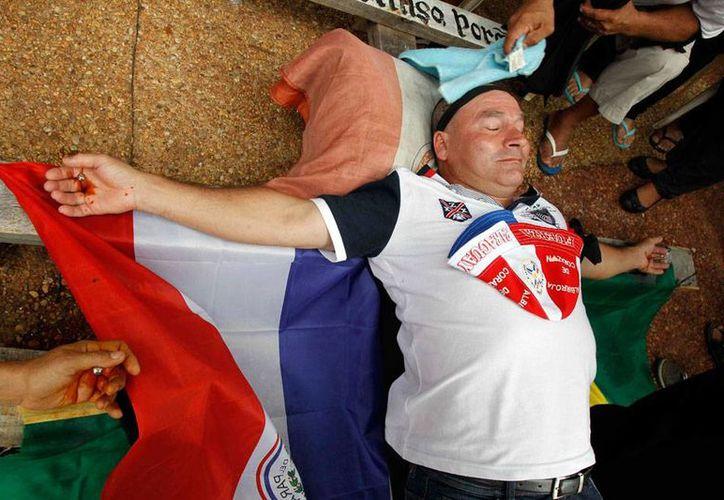 En Paraguay, extrabajadores de una planta de energía que exigen pagos de prestaciones se crucificaron a manera de protesta. (Archivo/Efe)