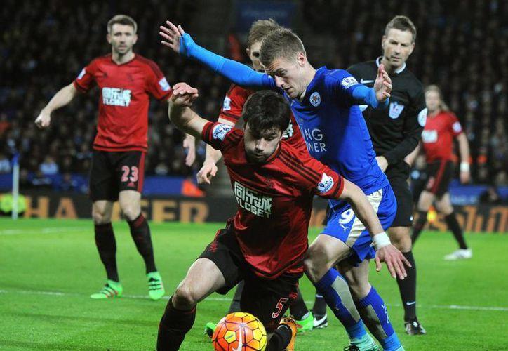 Jamie Vardy (de azul), goleador del Leicester y de la Liga Premier, disputa el esférico con Claudio Yacob, del West Brom. El partido terminó 2-2. (AP)