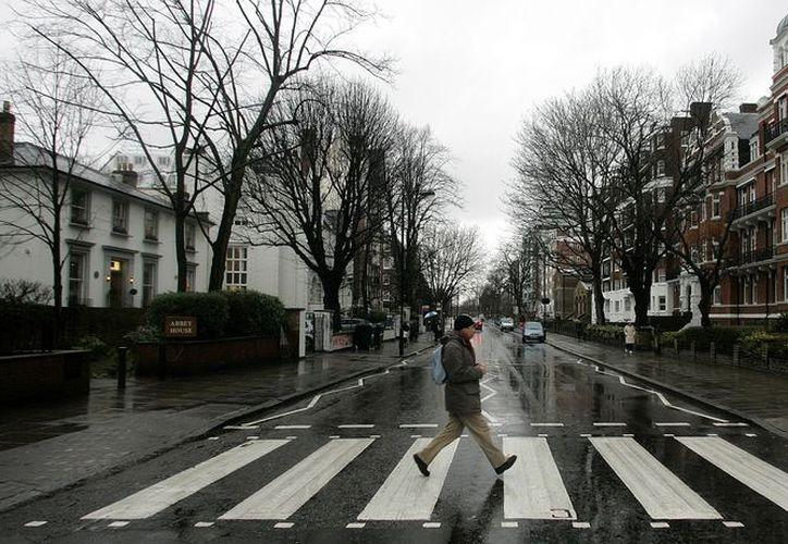Un hombre atraviesa la famosa calle que cruzaron los Beatles frente a los estudios Abbey Road. (Agencias)