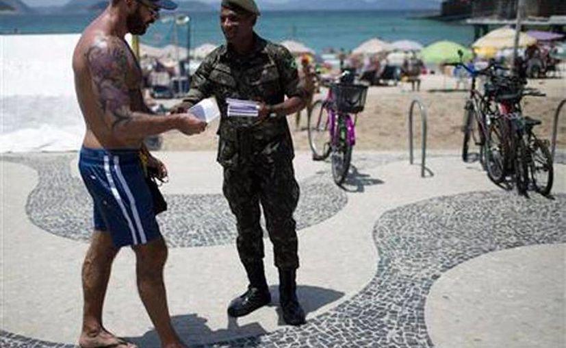 Un soldado distribuye información sobre el virus del zika en la playa de Copacabana, en Río de Janeiro. Evitar su transmisión e suna de las preocupaciones de cara a los Juegos Olímpicos. (AP)