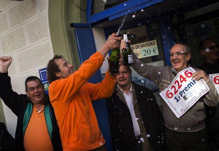 Trabajadores de una oficina de Lotería en Barcelona celebran el haber vendido el billete ganador del primer premio del sorteo de Navidad. (Agencias)