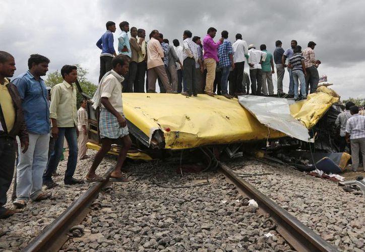 Indios permanece parados sobre los restos del autobús escolar que fue destrozado por un tren. (Foto: AP)