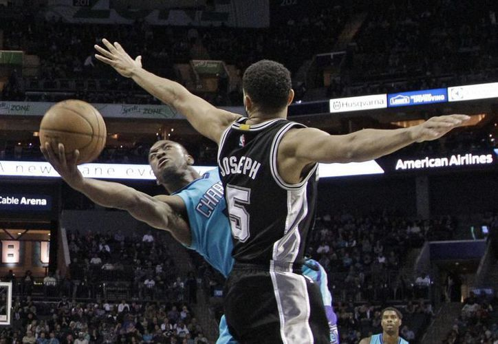Kemba Walker, de Hornets, dispara al aro pese a la marcación de Cory Joseph, de Spurs, conjunto que finalmente se llevó el triunfo. (Foto: AP)