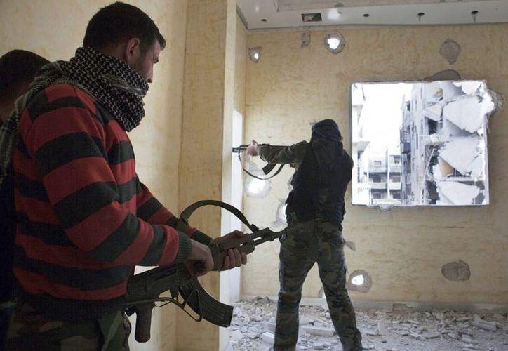 Dos combatientes del Ejército Libre Siro (ELS) rastrean un edificio en Alepo, Siria. (EFE)