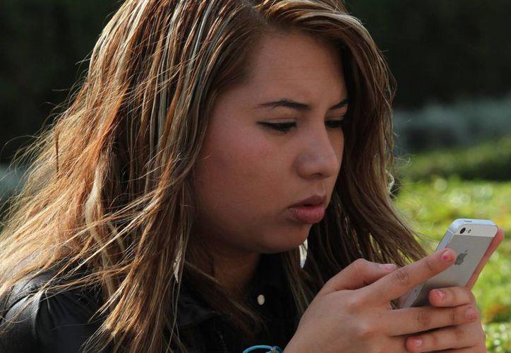 Una mala postura al utilizar el celular puede ocasionar dolores lumbares, en el cuello y tensiones musculares. (Archivo/Notimex)