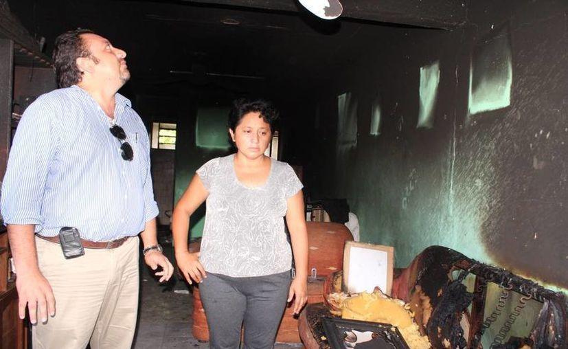 El diputado Francisco Torres Rivas y la señora Catalina Hoil supervisan los daños en la casa. (Cortesía)