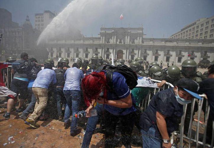 La policía antimotines dispersó a los manifestantes con gases lacrimógenos y chorros de agua. (AP/Luis Hidalgo)
