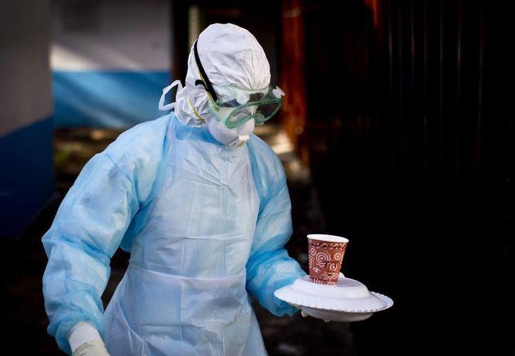 Un empleado médico con un traje especial traslada alimentos en el hospital Kenyatta National en Nairobi, Kenia, a un hombre en cuarentena debido a que se contagió del virus del ébola en Uganda. (Foto: AP)