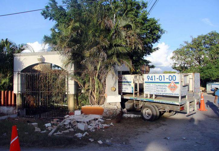 Una barda impidió que la camioneta repartidora de tanques de gas entrara por completo al domicilio. (Milenio Novedades)