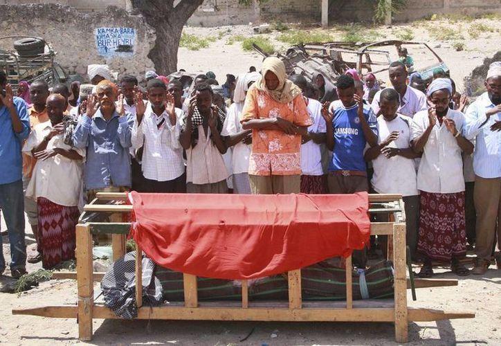 Somalíes rezan junto al cadáver de una de las seis personas fallecidas por fuego de mortero, en Mogadiscio. EFE/Archivo