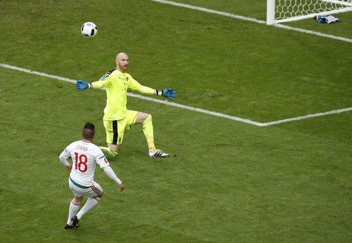 Momento exacto en que el húngaro Zoltan Stieber (i), después de una larga carrera, le hace un sombrerito al portero austriaco Robert Almer para anotar el segundo tanto magiar en partido del Grupo F de la Euro 2016 que quedó 2-0. (AP)