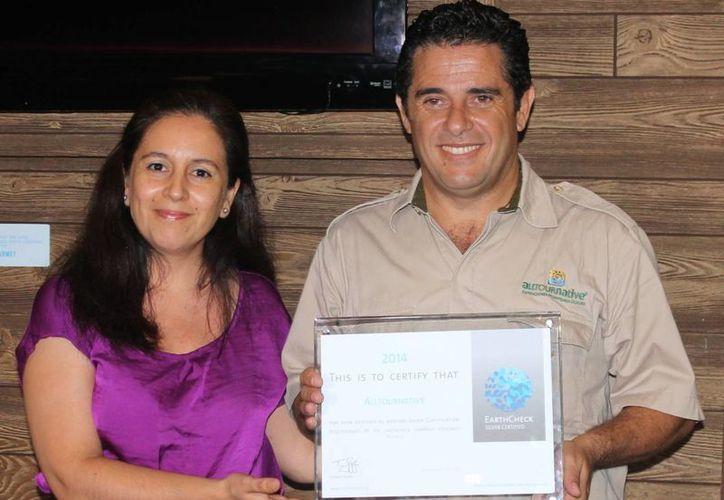 Erica Lobos, gerente regional de EarthCheck, y Carlos Marín Morales, director fundador de Alltournative, muestran la distinción. (Israel Leal/SIPSE)