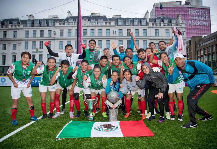 Seleccionados mexicanos mujeres y hombres celebran con sus trofeos la obtención de los dos campeonatos de la Homeless World Cup 2016. (Foto tomada de elpais.com)
