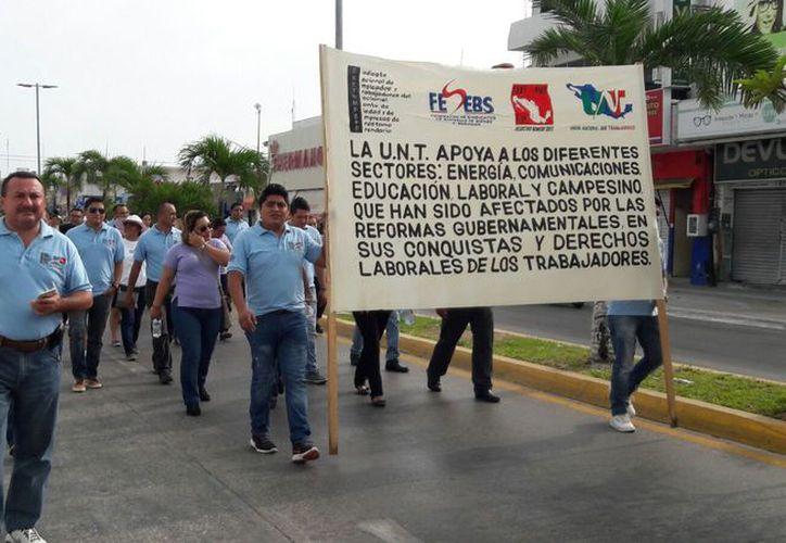 Durante el desfile, los trabajadores expusieron en mantas parte de sus reclamos a las autoridades, como la afectación a los derechos laborales resultado de las reformas gubernamentales. (Foto: Redacción / SIPSE)
