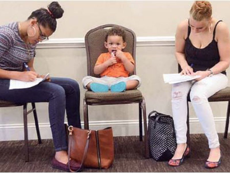 Joan Herrera, center, sits and waits as his mother Andrea Batista Garcia, left, and Marlene Gonzales, fill out job applications while attending the Great Northeast 2018 Job Fair at Capriotti's in McAdoo, near Hazleton, Pa.