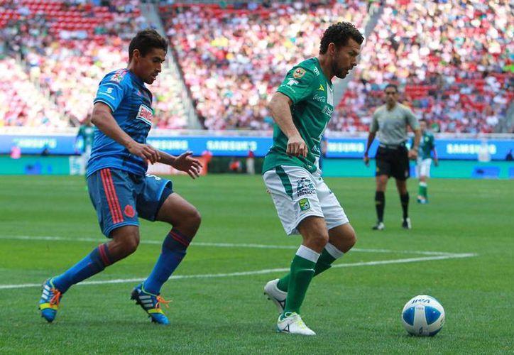 Chivas hizo el único gol del partido y se llevó 3 puntos como local, frente al actual monarca del futbol mexicano León. En la foto, Patricio Araujo (izq.), de Chivas y Miguel Sabah, del Leon, disputan la pelota. (Agencias)