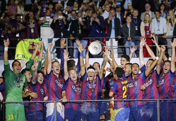 Barcelona y Sevilla definirán el primer título europeo del año al enfrentarse en la Supercopa de la UEFA. En la imagen se observa al club catalán levantando el trofeo de la Champions League 2015. (AP)