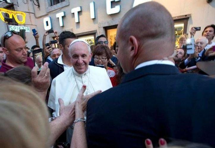 Muchos ciudadanos de Roma y turistas que se encontraban en la zona esperaron a que el Papa saliera de la óptica para tomarse fotos con él. (AP)