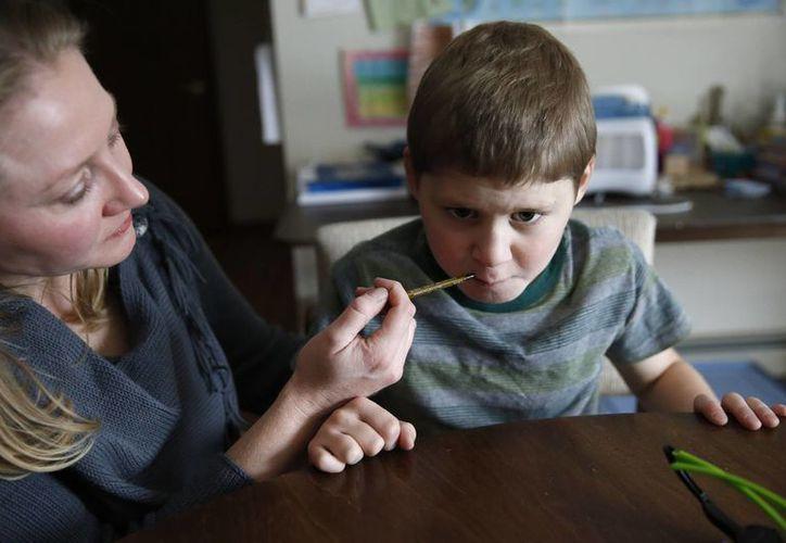 Nicole Gross suministra con una jeringa a su hijo Chase una dosis diaria de aceite de marihuana medicinal, en Colorado Springs, Colorado. (Agencias)