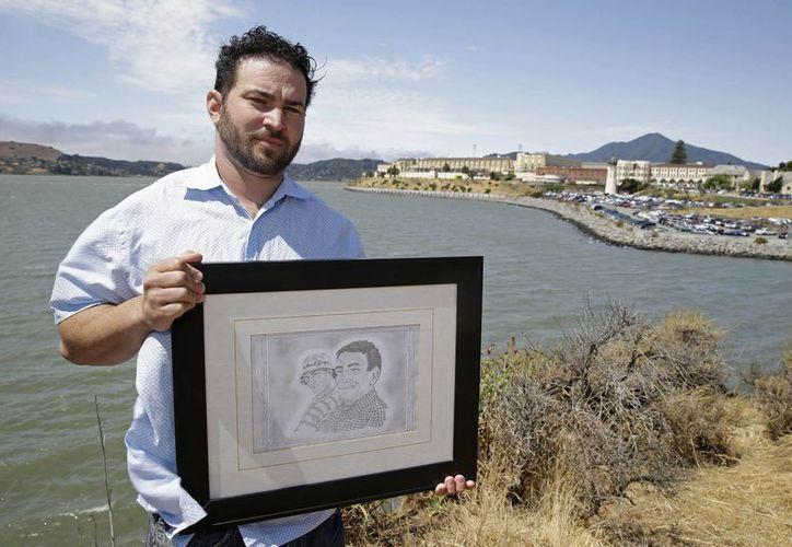 Dan Ager muestra un retrato a lápiz de él con su padre, frente a la prisión estatal de San Quentin, California. Ager fue asesinado en la prisión de Salinas Valley en 2010. (Agencias)