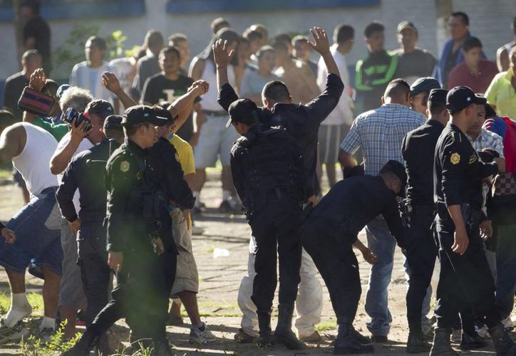 Policías revisan a presos luego que las autoridades tomaran el control de la cárcel la Granja de Rehabilitación Canadá, en Escuintla, Guatemala. (Agencias)