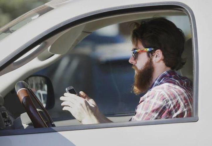 Un hombre usa su teléfono celular mientras conduce a través del tráfico en Dallas, Texas. (Archivo/AP)