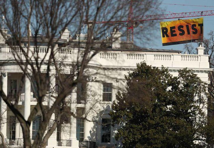 La pancarta desplegada por el grupo ambientalista Greenpeace, desde una grúa, frente a la Casa Blanca, el 25 de enero de 2017. (AP/Andrew Harnik)