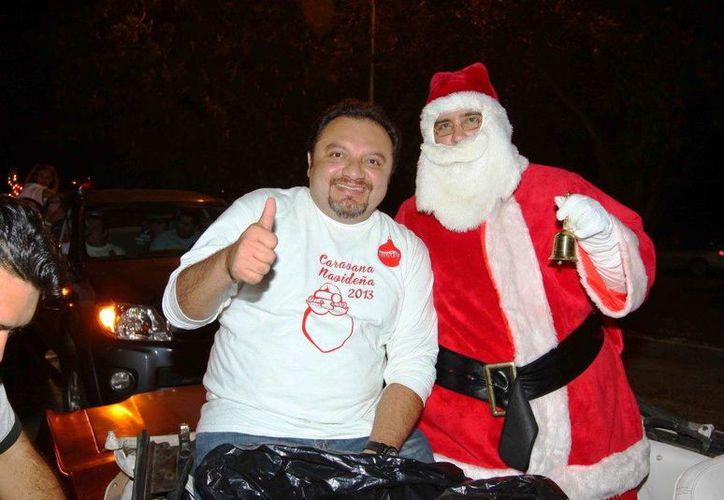 El diputado Francisco Torres Rivas acompañado de Santa Claus durante la caravana navideña. (SIPSE)
