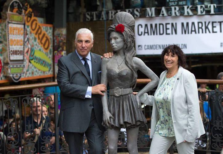 Mitch Winehouse y Janis Winehouse posan junto a la estatua de su hija, la fallecida cantante Amy Winehouse, que fue develada en el mercado de Camden en Londres, Inglaterra. (Agencias)