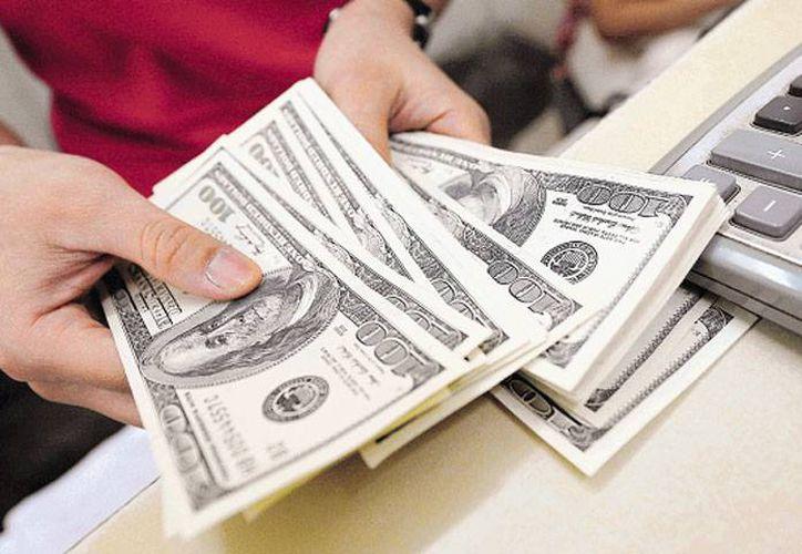 El dólar cerró a la compra en 14.23 pesos. (Archivo/AP)