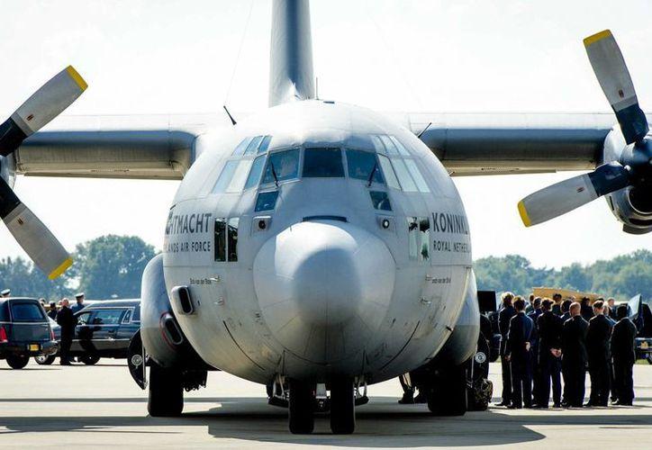 Imagen de los militares holandeses que reciben al avión con los restos de algunas de las 298 víctimas del desastre aéreo del vuelo de Malaysia Airlines en el este de Ucrania, procedente de Járkov, en la base militar de la ciudad holandesa de Eindhoven. (EFE)