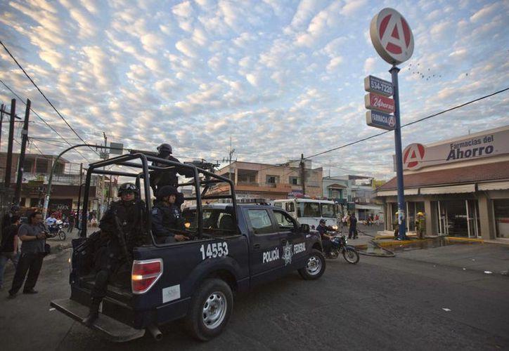 Policías federales llegan a una farmacia cercana al Palacio Municipal de Apatzingan, que fue atacada por desconocidos. (Agencias)