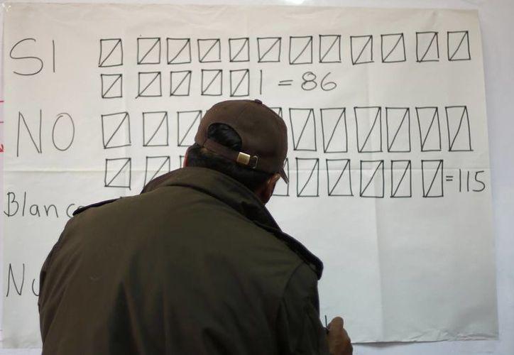 Un vocal de mesa lleva la contabilidad de la votación durante el recuento de los sufragios en el referendo para que los bolivianos decidieran si aprobaban o no una reforma constitucional en favor de la reelección presidencial en La Paz, Bolivia. (Agencias)