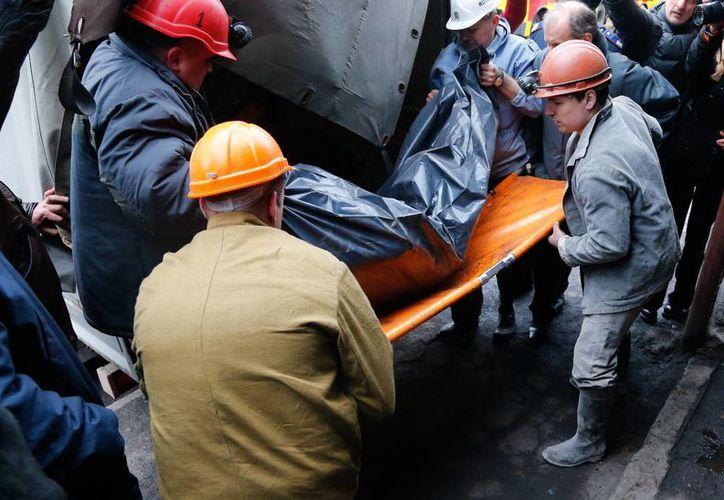 Rescatistas trasladan el cuerpo de una de las víctimas fatales de la explosión subterránea en Ucrania. (Agencias)