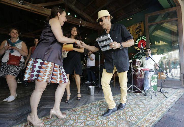 Un hombre baila con los visitantes al compás de la música cubana en un bar-lounge en el barrio de la Pequeña Habana de Miami, Florida, declarada tesoro nacional de Estados Unidos. (AP/Alan Diaz, Archivo)