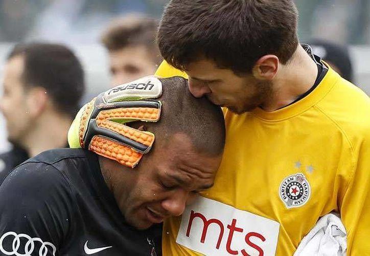 Cada que el futbolista Everton Luiz tocaba el balón se escuchaban gritos de mono desde la tribuna. En la foto, el brasileño es consolado por su compañero de club.(Archivo/AP)