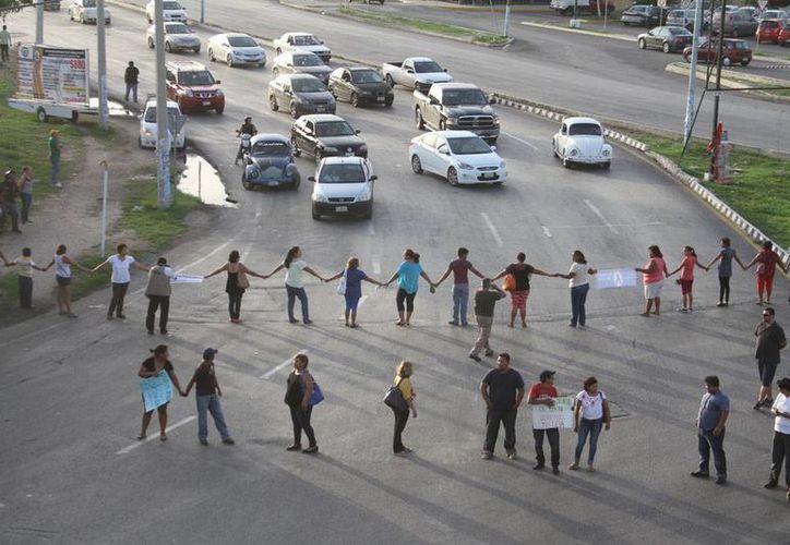 Vecinos de Ciudad Caucel cerraron el acceso a la zona, como protesta por lo que consideran un mal trabajo de los peritos, en un accidente en el que murió una mujer. (César González/SIPSE)