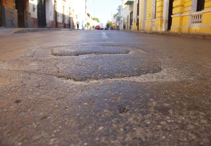 Montículos de asfalto endurecido y grietas se observan en calles del centro. (Milenio Novedades)