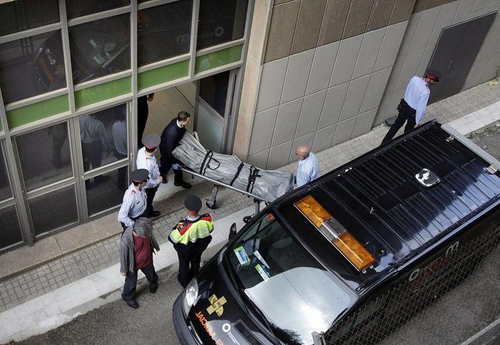 Personal de los Servicios Funerarios y del juzgado de guardia retiran el cadáver del profesor del IES Joan Fuster de Barcelona fallecido hoy a manos de un alumno de segundo de secundaria, que le disparó flechas de ballesta. (EFE)