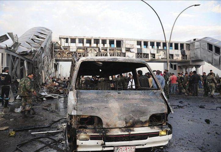 Imagen cedida por la Agencia oficial SANA de la zona de un ataque suicida en una estación de autobús de Damasco, Siria, el martes 26. Todas las armas químicas sirias deben ser destruidas a más tardar el próximo año. (EFE)