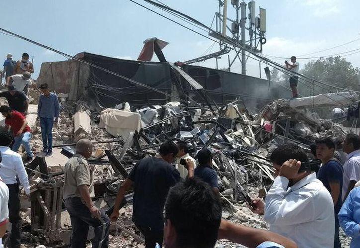 Varios rescatistas laboran para liberar a las personas que se encuentran dentro de los escombros. (Foto: Twitter)