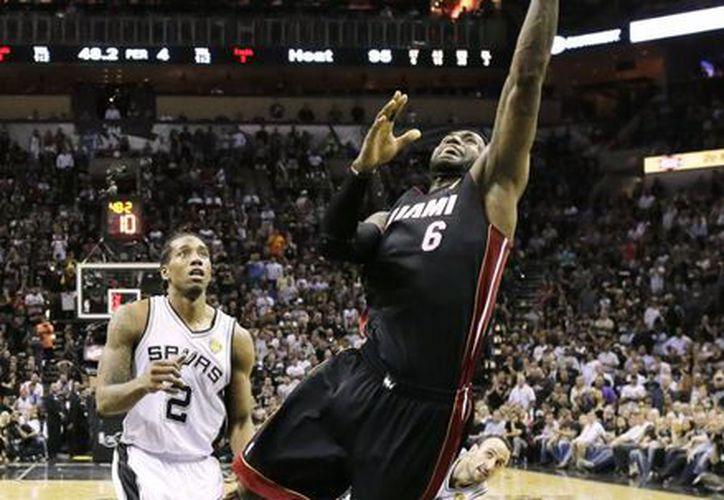 Le Bron James (6) anota pese a la marcación de Kawhi Leonard (2), de Spurs. (Foto: AP)