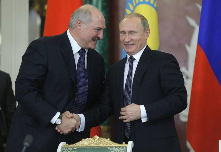 Los presidentes de Bielorrusia, Alexander Lukashenko, y de Rusia, Vladimir Putin, estrechan las manos en el Kremlin, el martes 23 de diciembre de 2014, en Moscú. (Foto AP/ Maxim Shipenkov)