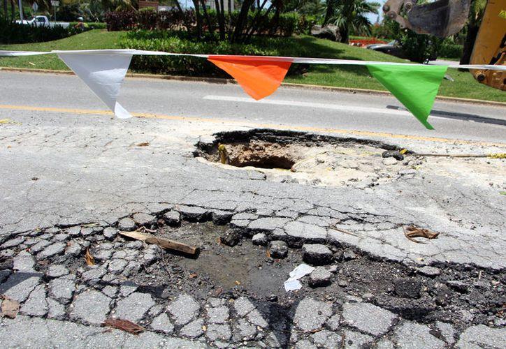 Elementos de la dependencia han realizado trabajos de bacheo desde hace semanas; sin embargo, las lluvias vuelven a dejar al descubierto los hoyos en el asfalto.  (Paola Chiomante/SIPSE)