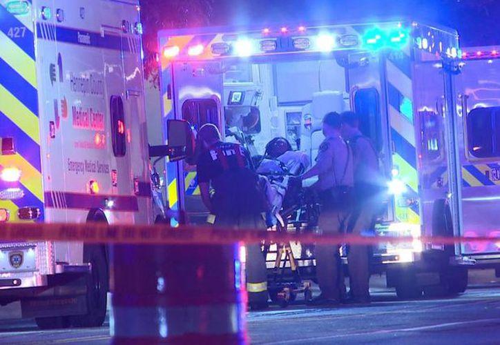Fotografía que muestra personal de urgencias trasladando a una persona a una ambulancia después de un tiroteo la madrugada en Minneapolis. (KARE vía AP)