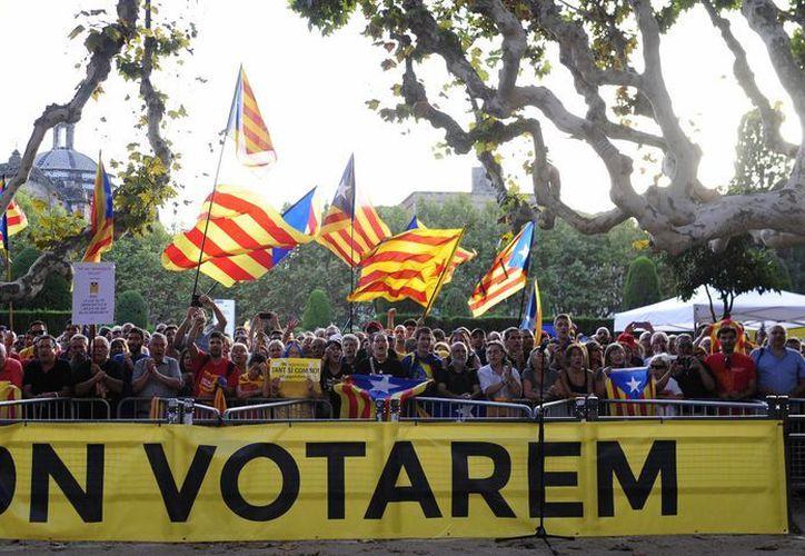 Cientos de personas ondean banderas  que simbolizan la independencia de Cataluña, en las afueras del Parlamento de Barcelona, durante una manifestación para pedir su separación de España. (Agencias)