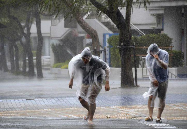 Paseantes en Naha, Okinawa, resienten los fuertes vientos que anuncian la aproximación del tifón que afecta Japón. (Foto: AP)
