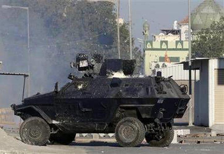 Un vehículo blindado de la policía, salpicado con bombas de pintura, lanza gas lacrimógeno contra manifestantes antigubernamentales en Sitra, Bahreín. (AP)