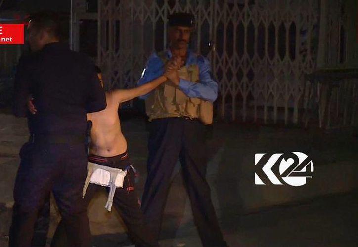 Imagen tomada de la señal de una televisota local que muestra a un niño siendo detenido por elementos de seguridad, uno de los cuales corta un cinturón con explosivos. (Canal 24 de la TV de Kurdistán vía AP)