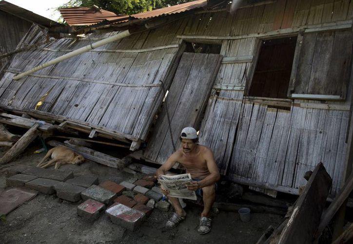 Un hombre  lee el periódico fuera de su casa destruida, una semana después del devastador terremoto en Pedernales, Ecuador. (Agencias)